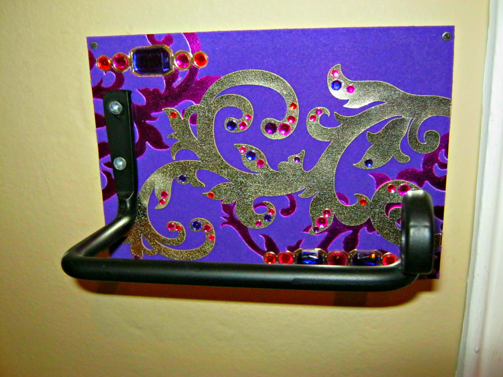 Hair appliance holder with greeting card backing tacked onto wall