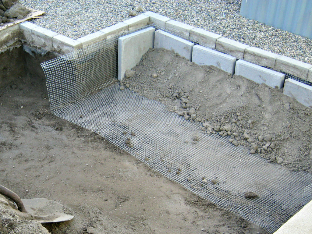 Hardware cloth held in place by pavers and dirt